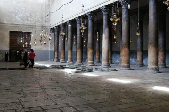 Interior of the Church of the Nativity, looking west down the nave. The trapdoors in the floor reveal 4th-century floor mosaic from the Constantinian Church