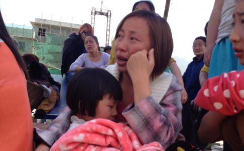 A woman weeps as she holds a young child in her arms in the earthquake-hit county of Luzhou, Sichuan Province on April 20. Photo: Simon Song