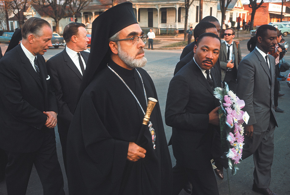 Archbishop Iakovos, Martin Luther King Jr., and other dignitaries walking to the Dallas County Courthouse to hang a funeral wreath in honor of Reverend James Reeb, a civil rights activist who was beaten and killed by white segregationists, Selma, Alabama, March 1965; photograph by Dan Budnik from his book Marching to the Freedom Dream, which includes an essay by Harry Belafonte and has just been published by Trolley